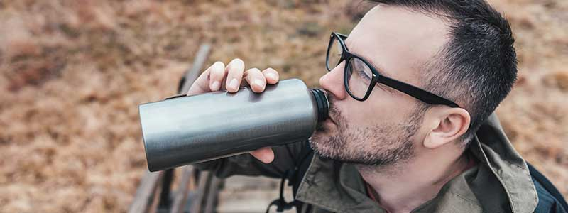 Man drinking water from a flask outdoors